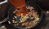 加入已熟的豬肉碎和一罐牛尾湯,快火煮6-7分鐘,加入黑椒碎做成肉醬汁。